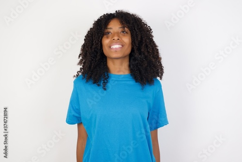 Young african woman with curly hair wearing casual blue shirt over white background with a happy and cool smile on face Fototapet