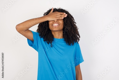 Photo Young african woman with curly hair wearing casual blue shirt smiling and laughing with hand on face covering eyes for surprise
