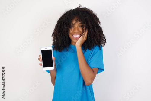Vászonkép Young african woman with curly hair wearing casual blue shirt hold hand modern t
