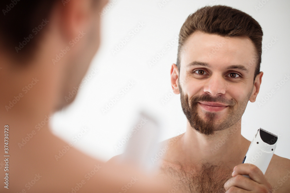 Fototapeta Handsome young man shaving his beard in the bathroom. Portrait of a stylish naked bearded man examining his face in-home mirror.