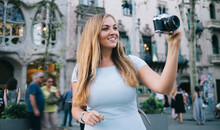 Cheerful Caucasian Tourist Using Vintage Technology For Photographing Architecture Landscape Near Casa Batllo In Barcelona, Carefree Woman Taking Pictures Of City Beauty In Hispanic Catalonia