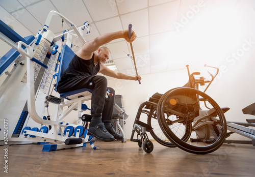 Photo Disabled man doing strength exercises separate from the wheelchair