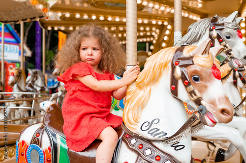 Fényképezés A little curly girl in a red dress sits on a horse in an amusement park on a car