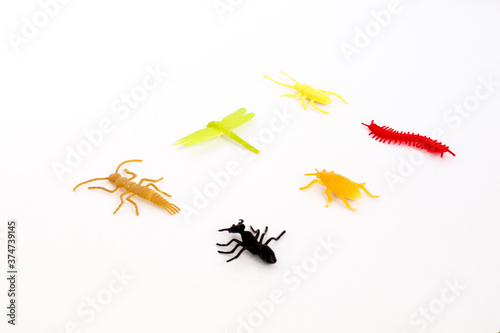 Fotografia, Obraz plastic toy insect on the white background, orange beetle tick, green caterpilla