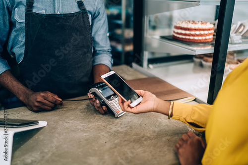 Tela Woman making payment with smartphone in cafe