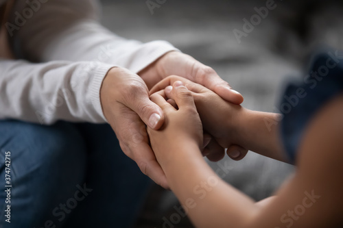 Photo Close up compassionate young foster parent holding hands of little kid girl, giving psychological help, supporting at home