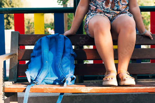 Fotomural Girl's legs and blue backpack on a bench. Back to school.