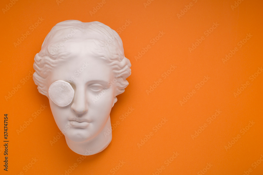 Fototapeta Aphrodite sculpture on yellow background, face cleaning, removing makeup.