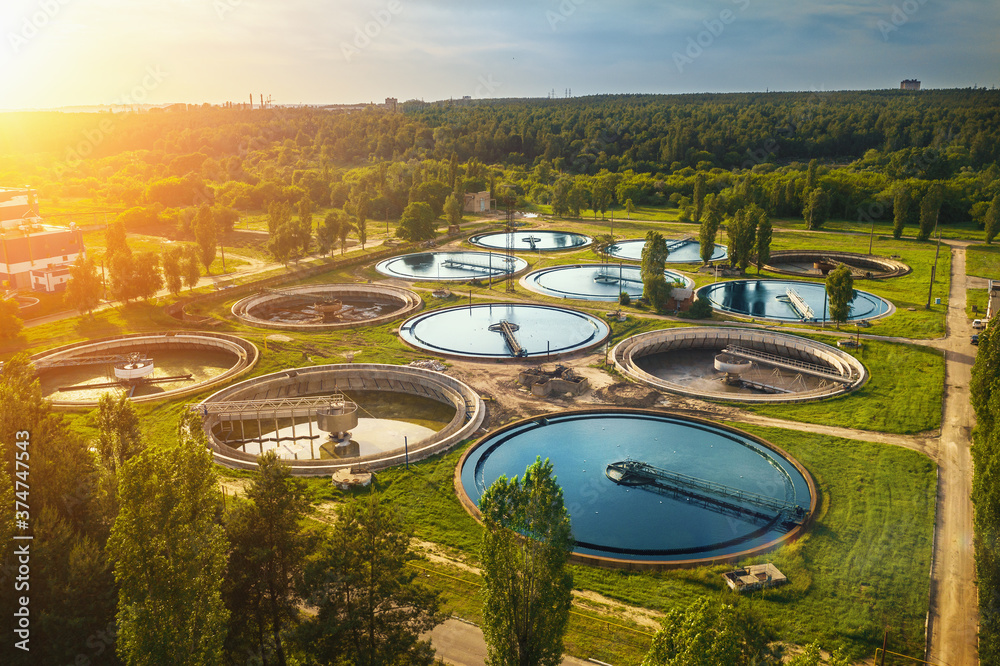 Fototapeta Aerial view of modern industrial sewage treatment plant at sunset.