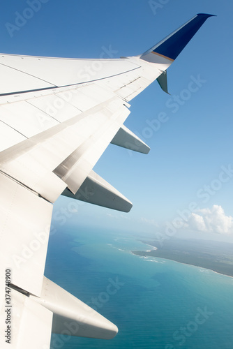 AIrplane wing with view of Caribbean water and and below. Fototapet