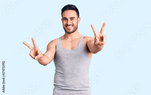 Fototapeta Young handsome man wearing swimwear and sleeveless t-shirt smiling with tongue out showing fingers of both hands doing victory sign