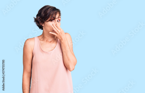 Beautiful young woman with short hair wearing casual style with sleeveless shirt smelling something stinky and disgusting, intolerable smell, holding breath with fingers on nose Canvas