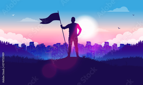 Fototapeta Man with raised flag in front of city and sunlight - Proud male on hilltop