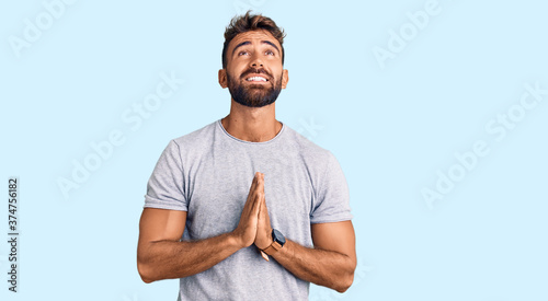Young hispanic man wearing casual clothes begging and praying with hands together with hope expression on face very emotional and worried Fototapete