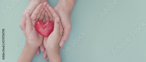 Carta da parati Adult and child hands holding red heart, organ donation, wellbeing, family healt