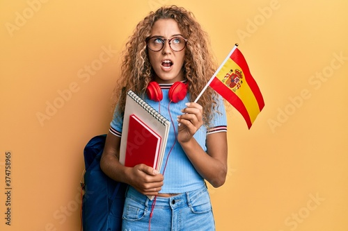 Fototapeta Beautiful caucasian teenager girl exchange student holding spanish flag angry and mad screaming frustrated and furious, shouting with anger
