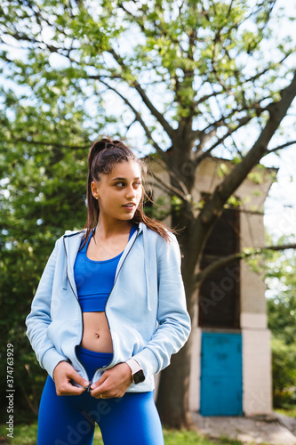 Fototapeta Fitness young woman posing on camera in the park