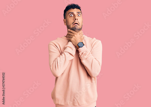 Young hispanic man wearing casual clothes shouting suffocate because painful strangle Canvas Print