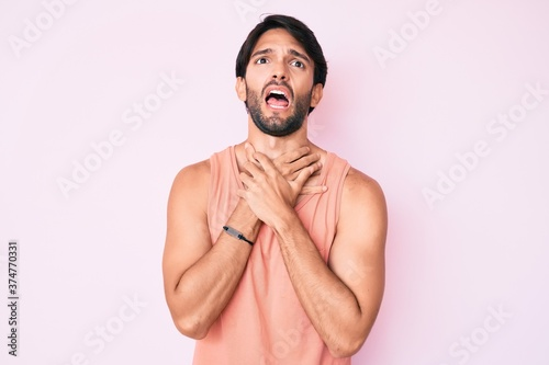 Photo Handsome hispanic man wearing casual clothes shouting and suffocate because painful strangle