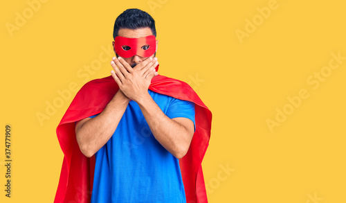 Young hispanic man wearing super hero costume shocked covering mouth with hands for mistake Billede på lærred