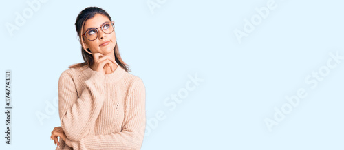 Fototapeta Young beautiful woman wearing casual winter sweater and glasses serious face thinking about question with hand on chin, thoughtful about confusing idea obraz