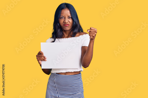 Fotografiet Young indian girl holding blank empty banner annoyed and frustrated shouting wit
