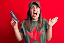 Young Beautiful Brunette Woman Wearing T-shirt With Red Star Communist Symbol Holding Gun Celebrating Achievement With Happy Smile And Winner Expression With Raised Hand