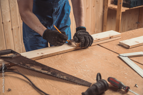 Fototapeta close-up of a male joiner measures with a ruler and a pencil dimensions are required for the product on a wooden table in the workshop obraz na płótnie