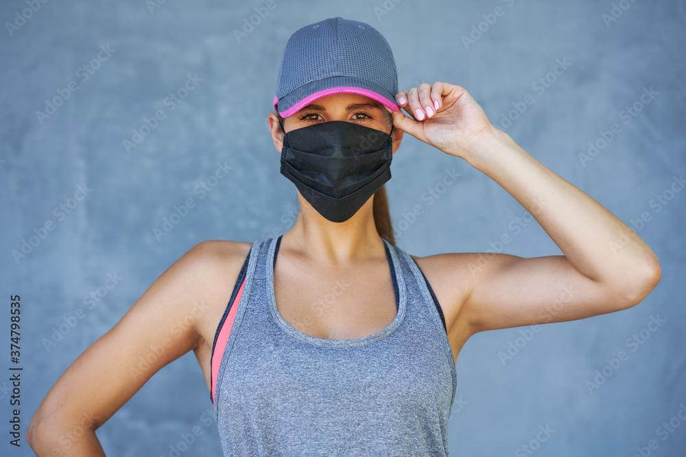 Fototapeta Female runner using protective mask during coronavirus pandemic