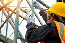 Asian Worker Wear Safety Height Equipment. Fall Arrestor Device For Worker With Hooks For Safety Body Harness, Worker As In The Construction Site