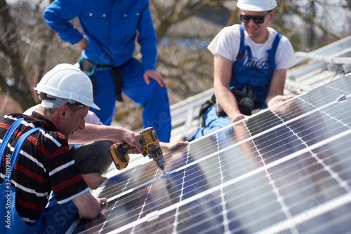 Carta da parati Male engineers installing solar photovoltaic panel system using screwdriver