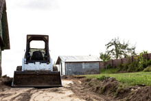 A Skid Steer Loader Clears The Site For Construction. Land Work By The Territory Improvement. Machine For Work In Confined Areas. Small Tractor With A Bucket For Moving Soil And Bulk Materials.