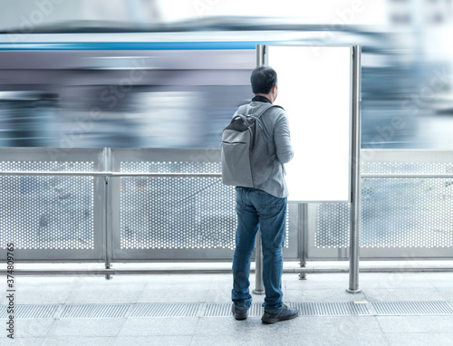 Fotografie, Obraz Traveler asian man with backpack looking blank signboard public for information tourism travel in subway train station with copy space for text