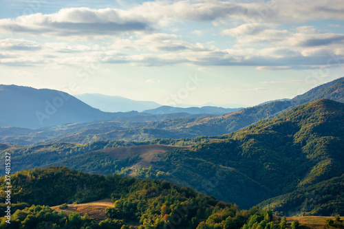 mountainous countryside in the afternoon. beautiful landscape of carpathians. valley of borzhava ridge in the distance. clouds on the sky. sunny weather