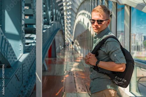 Cuadros en Lienzo A young man in sunglasses and a shirt walks along a modern glass business corrid