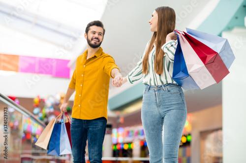 Fotografia Portrait of positive cheerful dreamy couple man woman go walk in shopping center