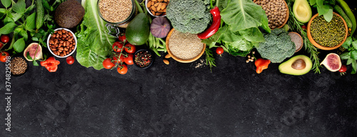 Foto Fresh vegetables, fruits and cereals on a black background, top view, copy space