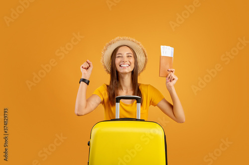Fotografie, Obraz Excited girl with luggage holding passport and flight tickets