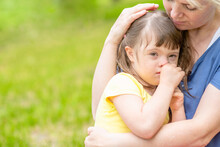 Happy Little Girl With Syndrom Down Hugs Mother In A Sunny Summer Park. Empty Space For Text