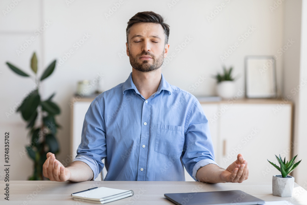 Fototapeta Office Zen. Relaxed Male Entrepreneur Meditating At Workplace, Coping With Work Stress