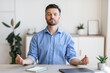 Office Zen. Relaxed Male Entrepreneur Meditating At Workplace, Coping With Work Stress