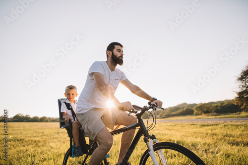 Father and his son cycling together outdoors Billede på lærred
