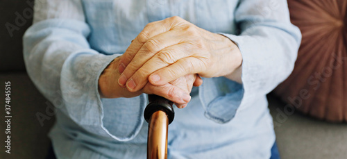 Elderly woman sitting in nursing home room holding walking quad cane with wrinkled hand Canvas