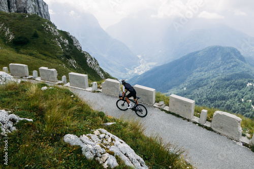 Obraz na plátně Professional road cyclists on lightweight bicycle ride up epic mountain road in alps