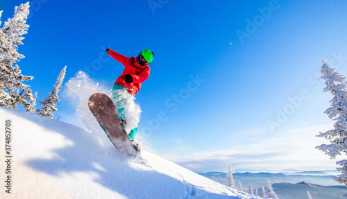 Fotografia Snowboarder jumping through air with deep blue sky in background, Freeride winte
