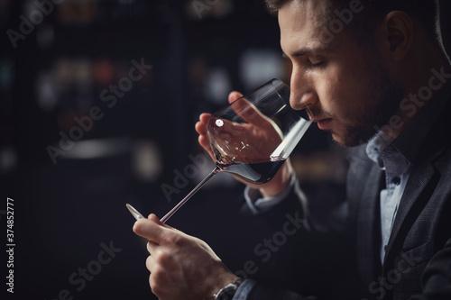 Fototapeta Sommeliers male hold glass red wine tasting degustation card