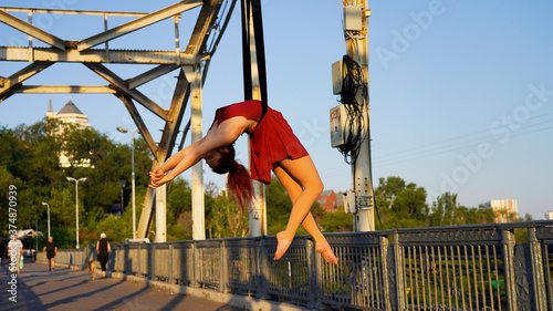 Canvas Circus performer on aerial straps performs an aerial act at dawn