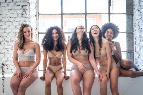 Fototapeta Group of women with different body and ethnicity posing together to show the woman power and strength. Curvy and skinny kind of female body concept obraz