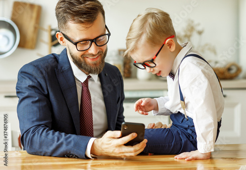 businessman father with a young schoolboy son looking at a smartphone Canvas Print