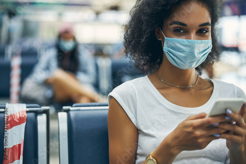 Happy smiling young woman in protective mask looking at the camera Fototapet